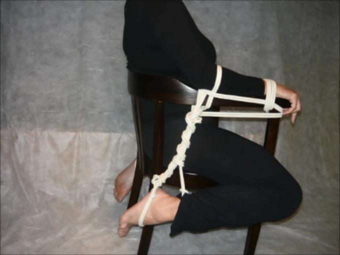 Związanie na krześle z nogami ułożonymi pod oparciem